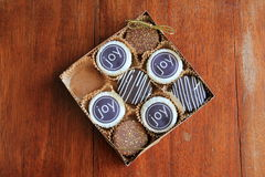 Box of gaily decorated cookies covered in chocolate Royalty Free Stock Photography