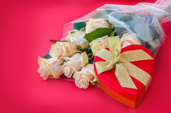 Box with a gift on a background of a bouquet of roses Stock Photography