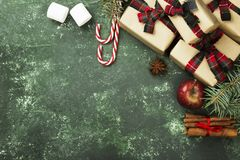 Box with gift for Christmas and various attributes of holiday on. A green background. Top view, copy space Stock Images