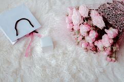 Box with a gift, a package, a perfume and a bouquet of pink roses stock photo