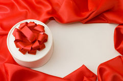 Box with a gift on a red fabric Stock Photos