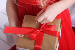 Box with a gift tied with red ribbon. Children's hands holding a gift and a pen writing something Royalty Free Stock Photo