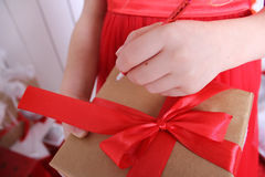 Box with a gift tied with red ribbon. Children's hands holding a gift and a pen writing something Royalty Free Stock Image