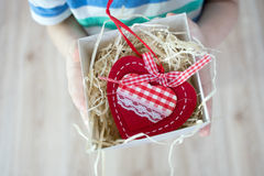 Box with a gift valentine heart in a child& x27;s hand on Valentine& x27;s Royalty Free Stock Photos