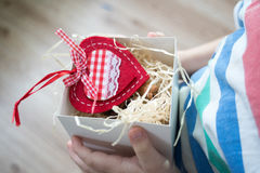 Box with a gift valentine heart in a child& x27;s hand on Valentine& x27;s Stock Photo