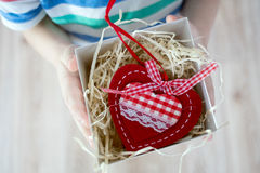 Box with a gift valentine heart in a child& x27;s hand on Valentine& x27;s Stock Photos