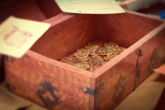 Box of gold coins. A wooden box with gold coins inside Royalty Free Stock Image