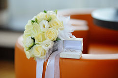 Box with gold wedding rings and a bouquet of white roses Stock Images