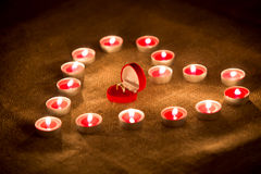 Box with golden ring lying in heart made of candles Royalty Free Stock Photography