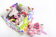 Box with hair accessories. Box with elastic bandages, buckles and bows inside and outside, on a white background Stock Images