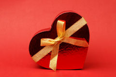 Box in heart shape with bow on red background Royalty Free Stock Photography