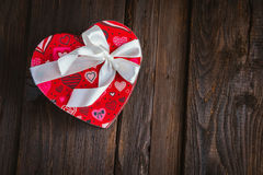 Box in heart shape. Red gift box with white bow heart shaped for Valentine's day on brown background Stock Images