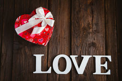Box in heart shape. Red gift box with white bow heart shaped for Valentine's day on brown background Stock Photos