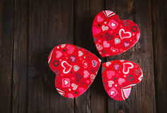 Box in heart shape. Red gift box with white bow heart shaped for Valentine's day on brown background Stock Image