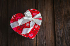 Box in heart shape. Red gift box with white bow heart shaped for Valentine's day on brown background Stock Photography