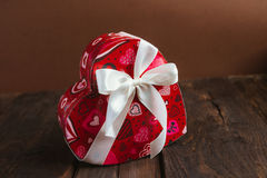 Box in heart shape. Red gift box with white bow heart shaped for Valentine's day on brown background Royalty Free Stock Photography