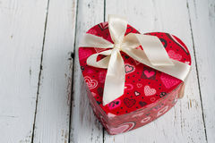Box heart shaped on white table. Red gift box in the shape of heart with bow on a white table Stock Photography