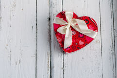 Box heart shaped on white table. Red gift box in the shape of heart with bow on a white table Royalty Free Stock Photo