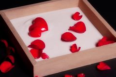 Framed box with sand and rose petals. Red hearts and rose petals in box isolated on black background royalty free stock images