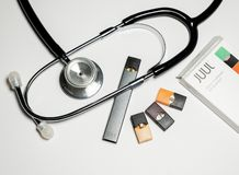 Free Box Holding JUUL Nicotine Dispenser And Pods With Stethoscope Royalty Free Stock Photo - 157047695