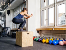 Box jump at the gym. Photo of a young woman doing a box jump at the gym Royalty Free Stock Image
