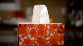 Box of kleenex. Colorful box of kleenex on a table top, with one sheet sticking out Stock Photo
