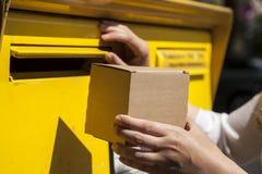 Box into mailbox Stock Photography