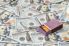 Box with matches on dollars. Wooden open box of matches lying on a pile of money stock photo