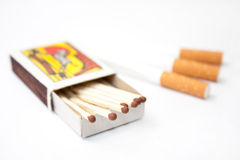 Box of matches and filter cigarettes in the background Stock Photos