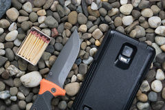 Box with matches, folding knife and smartphone Royalty Free Stock Photo
