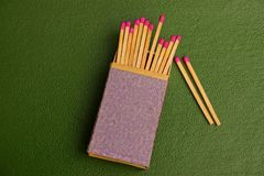 Box of matches with matches on a green background. Paper box with a set of matches Royalty Free Stock Images