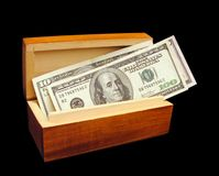 Box with money. Wooden box with money over black background Stock Image