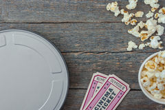 A box of movie, tickets and popcorn. Tin box with movie tickets to the cinema and pack with popcorn stand on a wooden table Stock Images