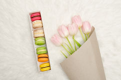 Box of multicolored macaroons and pink tulips on white fur, top view Stock Image