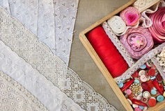 Box for needlework. Wooden box with buttons and ribbons on a lace background Stock Photography