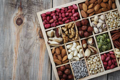 Box of nuts on a wooden table with space for text stock photo