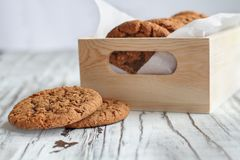 Box of Fresh Oatmeal cookies. Box of fresh homemade oatmeal cookies on a white table against a white background.. Selective focus on two lying on table royalty free stock images