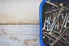 Box of old rusty metal screws on wooden background Stock Photography