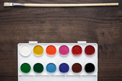 Box of paints and a brush on the table Royalty Free Stock Photo