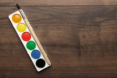 Box of paints and a brush on the table Royalty Free Stock Image