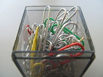 A box of paperclips. A closeup of paper clips of different colours and sizes in a clear plastic holder Royalty Free Stock Photos