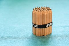 Bunch of pencils on the linen tablecloth. Compressed stationery rubber band, for pencils. royalty free stock images