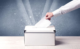 Box with person casting vote on sparkling background Royalty Free Stock Images