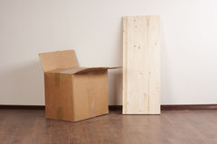 A box and a piece of wood. Carton box and a piece of wood Royalty Free Stock Photos