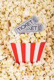Box of popcorn with movie tickets. On a background of spilled popcorn Royalty Free Stock Photos