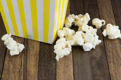 A box of popcorn on wooden background royalty free stock photography