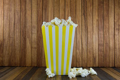 A box of popcorn on wooden background stock photography