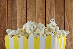 A box of popcorn on wooden background royalty free stock image
