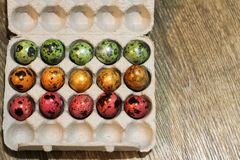 Box with the quail eggs painted different colors. holiday Easter. top view. wooden background royalty free stock photo