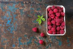 Box of raspberries. Paper market box of fresh raspberries with leaves over old wooden textured background. Top view with copy space Royalty Free Stock Images